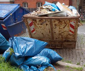 Müll-/Baucontainer mit Müllsäcken davor