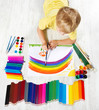 Child painting picture with brush in album using a lot of paints