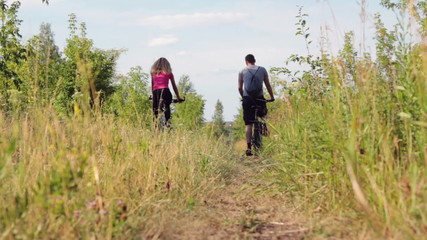 Back view of sporty couple riding bicycles  in the forest