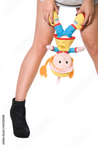 Doll hangs on a hand at girl between feet