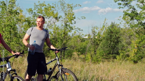 Attractive couple walking with bicycles and drinking water