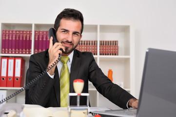 Junger Geschäftsmann im Büro telefoniert