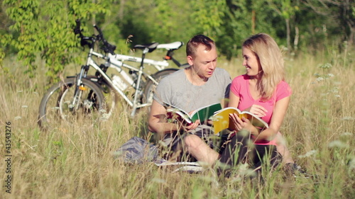 Attractive couple holding books during studying in the park