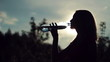 Silhouette of sporty young woman drinking mineral water