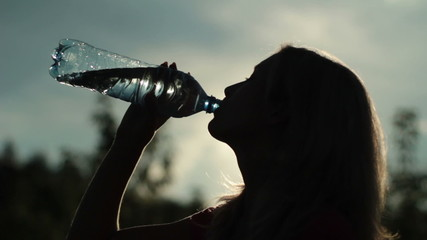 Silhouette of young woman drinking water over sunset