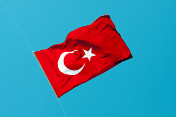 Waving flag of Turkey under sunny blue sky