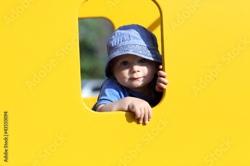Child in yellow toy house