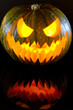 Halloween pumpkin with scary face with reflection on black glass