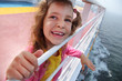 Little beautiful girl stands on board of large ship