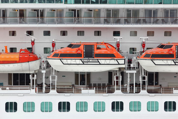 Orange lifeboats installed on beautiful white passenger liner