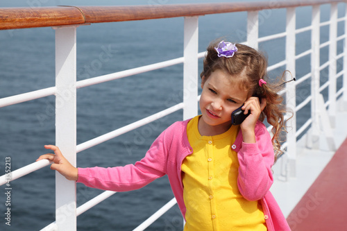 girl stands on board ship and talks by portable radio phone