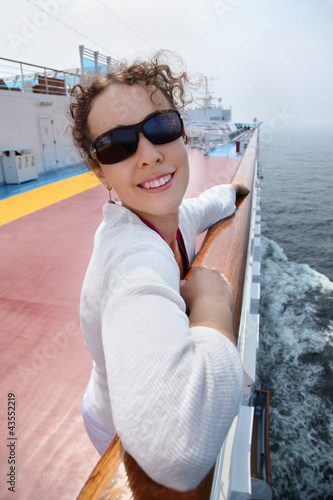 Beautiful woman stands on board of large ship,