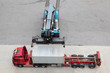 Crane moves and loads container to big truck, view from above