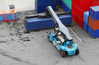 Small crane lifts large weight blue container, view from above
