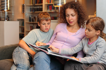 Son and daughter with their mother sit on sofa and read book