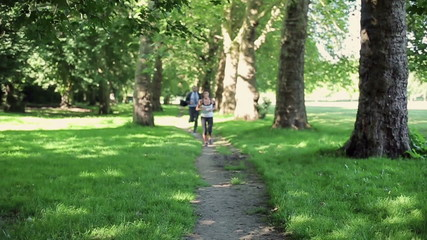 Businessman and woman jogging in park, slow motion