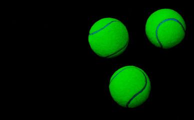 Drei neongrüne Tennisbälle in der Nacht