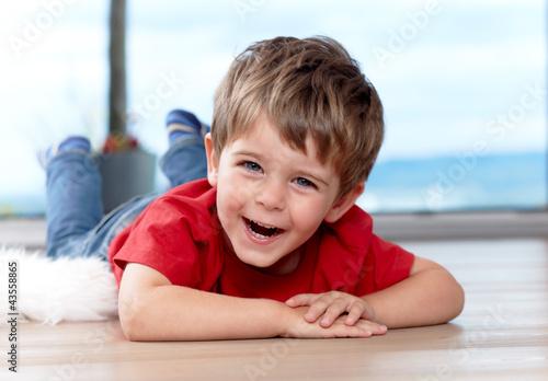 Leinwandbild Motiv three years old boy on the floor, having fun