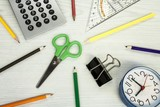 school composition, clock, pencils, calculator,  and scissors