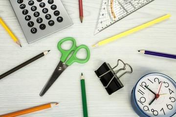 school composition, clock, pencils, calculator,  and scissors