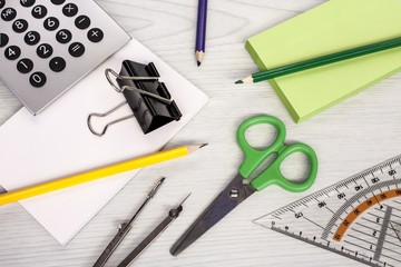 office composition, calculator, pencils, scissors and notepads