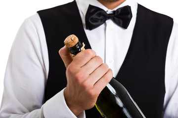 Waiter uncorking a champagne bottle