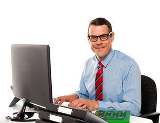 Happy young corporate man using computer