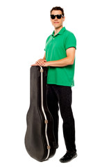 Trendy young man posing with guitar case