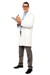 Young physician writing medical report