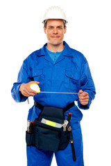 Male worker stretching measuring tape