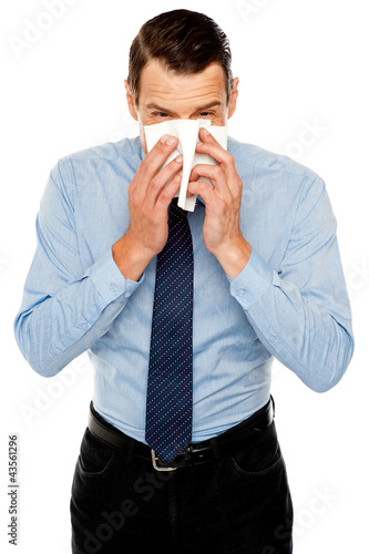 Young man having severe cold. Sneezing