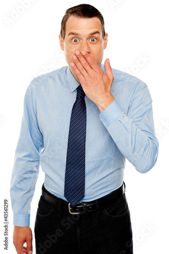 Surprised businessman with hand on mouth