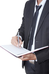 Businessman writing on notebook.