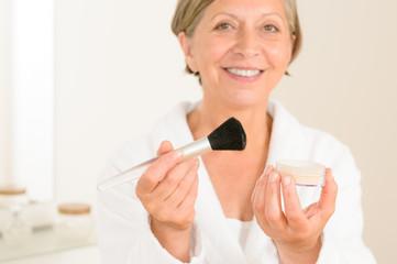 Mature woman hold brush and make-up powder