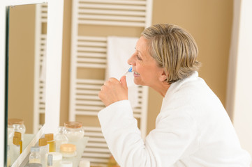 Senior woman brushing teeth in bathroom