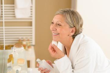 Senior woman apply face cream cotton pad
