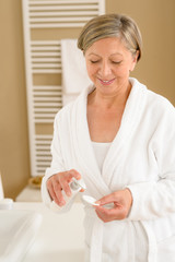 Senior woman bathroom apply face make-up removal