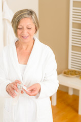 Senior woman bathroom apply cream cotton pad