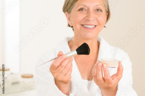 Mature woman hold brush and make-up powder