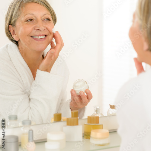 Senior woman apply anti-wrinkles cream look mirror