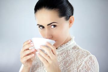 Pewna siebie kobieta pijąca aromatyczną herbatę z cukrem
