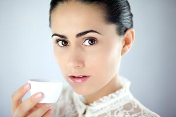 Intygująca kobieta trzymająca białą porcelanową filiżankę
