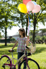 Little girl with bike and balloons