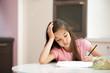 Exhausted little girl studying
