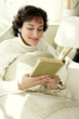 A lady sitting on the bed reading a book