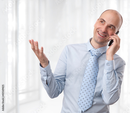 businessman smiling and talking on phone at office