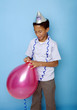 Boy tying up a blown balloon