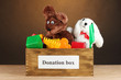 Donation box with children's toys on brown background close-up