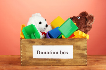 Donation box with children toys on red background close-up
