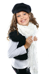 A little beautiful girl is in autumn clothes on a white
